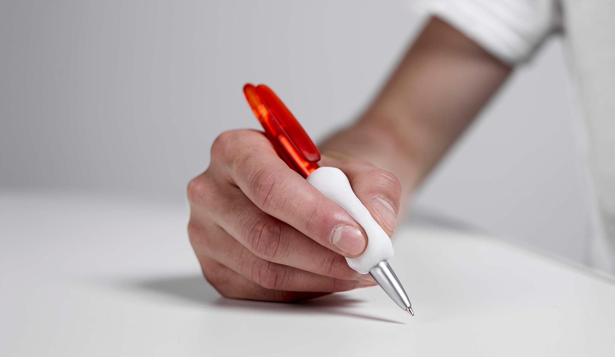 A hand holding a pen with a grip in Allfit.