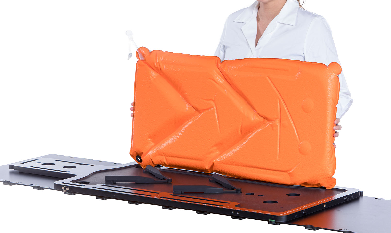 Woman holding an Orange Orfit Vacuum Bag over a baseplate with two indexing bars.