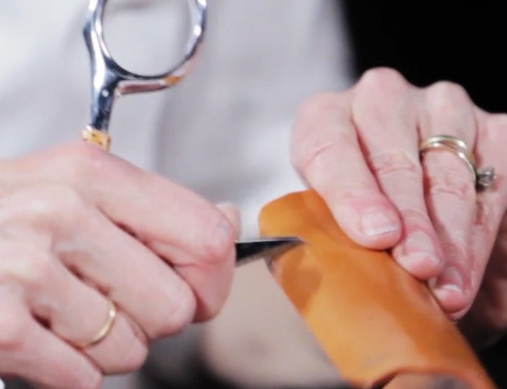 Scraping the coating off a thermoplastic orthosis to facilitate the adherence of hook-and-loop strapping.